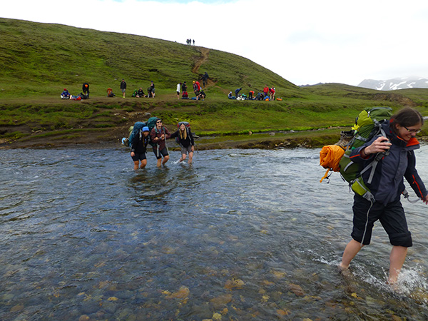 Students wading through Iceland glacial stream